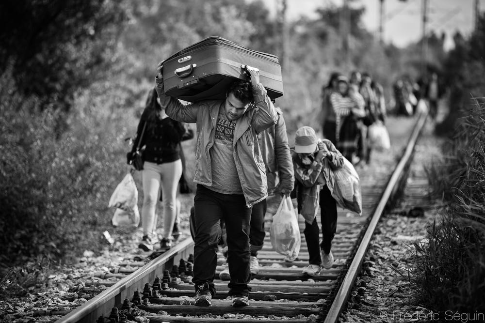 Emportant toute sa vie avec lui; les biens matériels sur l'épaule et la famille derrière, cet homme marche les derniers mètres pour arriver en Serbie et poursuivre le périple. Frontière Serbe- Macédonienne.