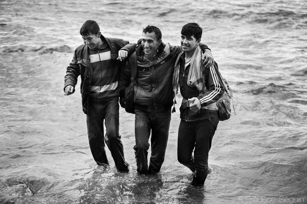 A group of men who just arrived on pneumatic boat are posing for a picture in the sea instead of  getting to the shores and drying themselves. The arrivals are not always tragic. Skala Sikamineas, Lesvos Island, Greece.