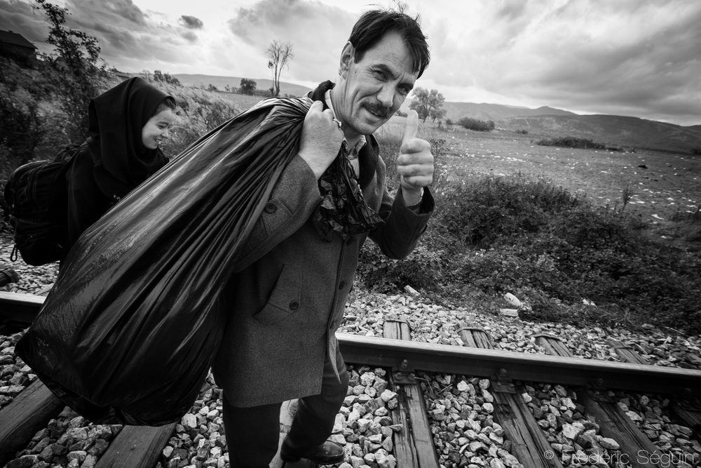 A father carries his family belongings as he walks alongside his daughter towards Serbia and a new life. Serbia-Macedonia border.