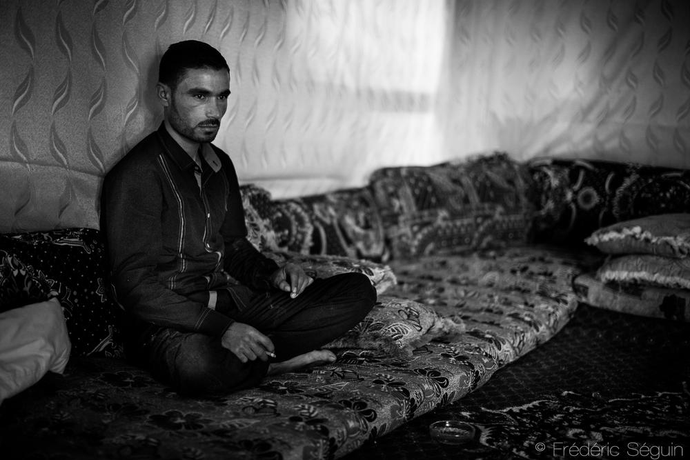 Un homme est en deuil dans sa tente d'un camp de réfugiés improvisé. Le décès d'un proche en Syrie illustre encore plus le fait qu'il est dangereux d'y rester et ardu de commencer une nouvelle vie au Liban. Vallée de la Bekaa, Liban.