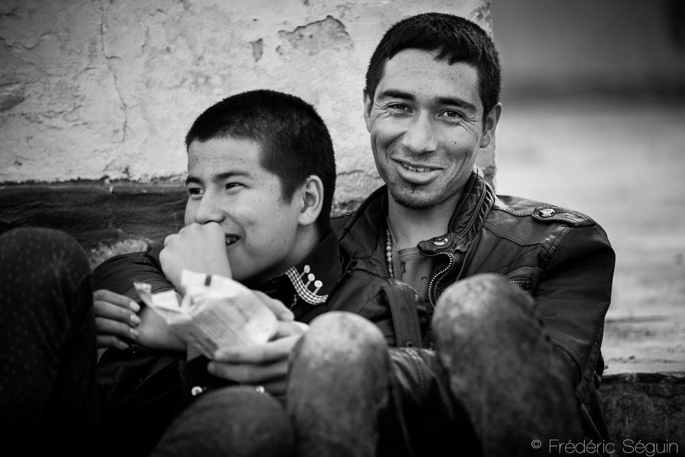 Deux proches gardent le sourire lors de la très longue attente pour leur enregistrement au camp de Moria. Peu de réfugiés restent seuls, des liens se créent entre inconnus et leur permettre de s'entre-aider dans cette épreuve qu'est l'exil. Moria, Lesvos, Grèce.