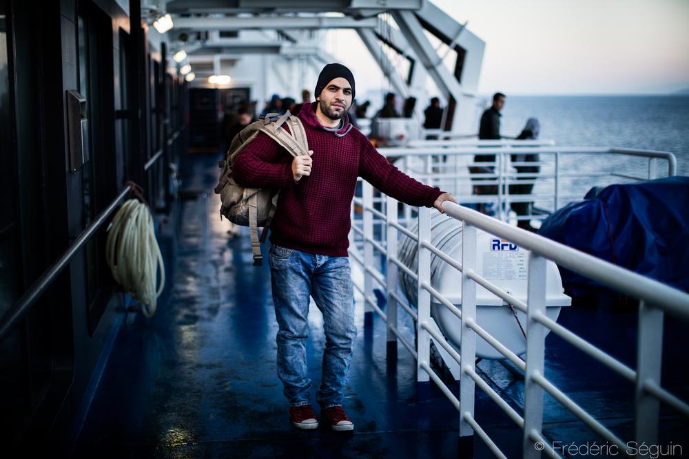 Amjad, réfugié iraquien regarde le levée de soleil sur une nouvellevie à l'arrivée du traversier au port de Piraeus.Mer Égée, Grèce.