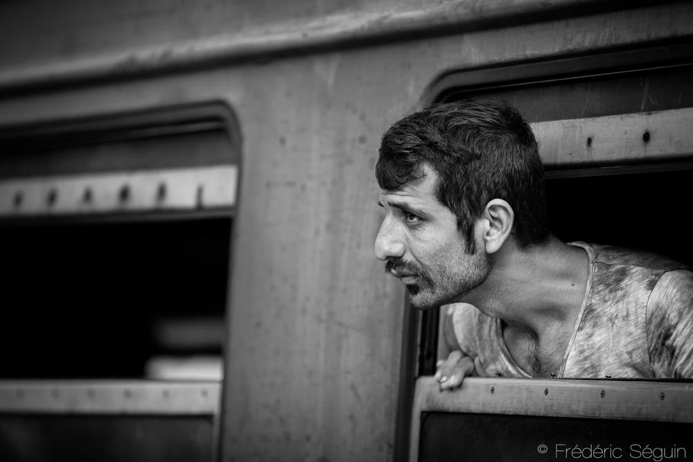 Un homme regarde à l'extérieur du train qui le mène au nord de la Macédoine. Il devra par la suite traverser la frontière Serbe à pied, ce qui ne pose habituellement aucun problème pour les adultes. Tabanovce, Macédoine (ARYM)