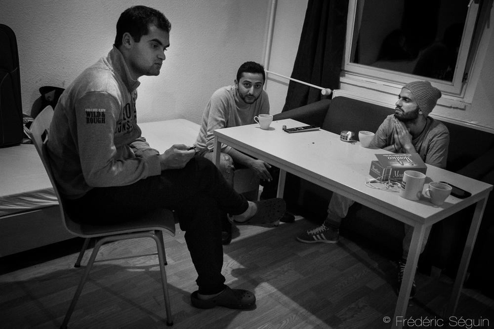 Salim, Ammer et Gaith discutent dans l'appartement qu'ils partagent. Ils ont un toit et une sécurité, leur nouvelle vie débute tranquillement.Brandenburg SchesViertel, Allemagne
