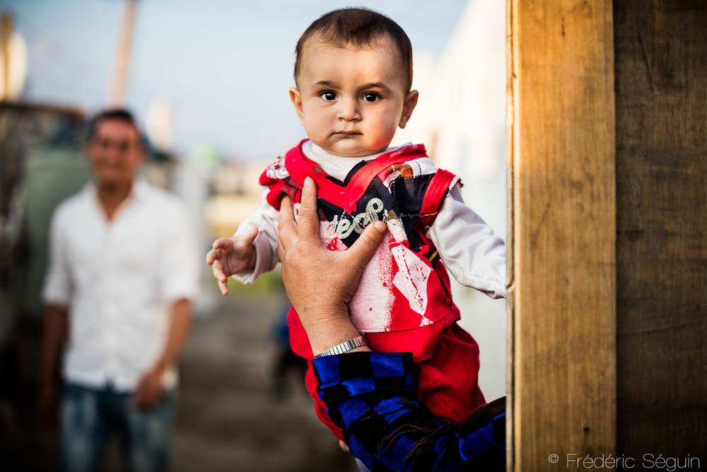 A mother in a refugee camp holds her son to be photographed but hides herself. Bekaa Valley, Lebanon.