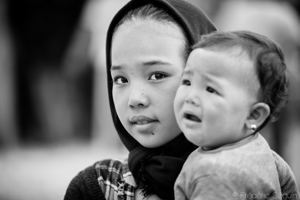 A young Afghan girl carries her sibling in her arms. Gevgelija, Macedonia (FYROM).