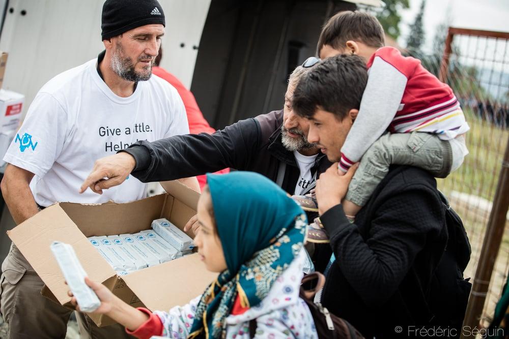Un bénévole de l'organisme NuN Civil Association distribue des paquets de biscuites réfugiés arrivant dans le camp de Gevgelija. Gevgelija, Macédoine.
