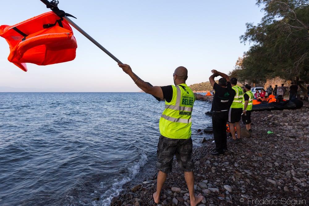 Des bénévoles d'Islamic Relief font signe aux bateaux arrivant l'endroit approprié pour débarquer. Lesvos, Grèce.