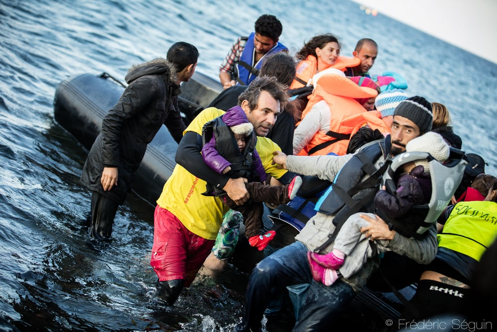 Un secouriste bénévole du groupe espagnol Proactiva aide un enfant réfugié à sortir de son bateau pneumatique pour ateindre la côte grecque. Lesvos, Grèce.