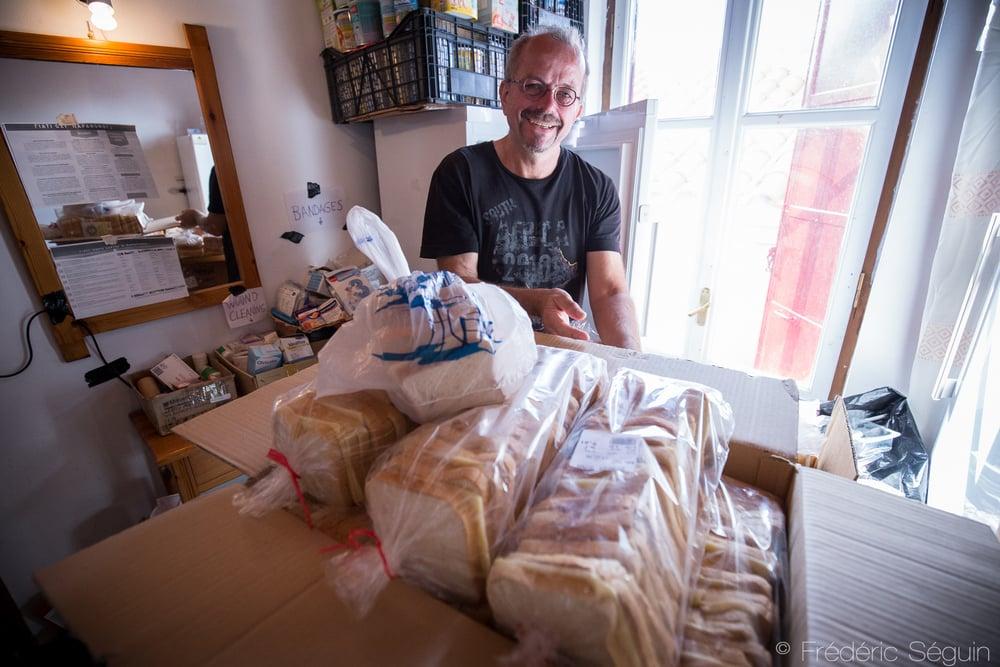 Un bénévole du groupe Starfish prépare en coulisses les centaines de sandwichs qui seront distribués à chaque jour aux réfugiés. Lesvos, Grèce.