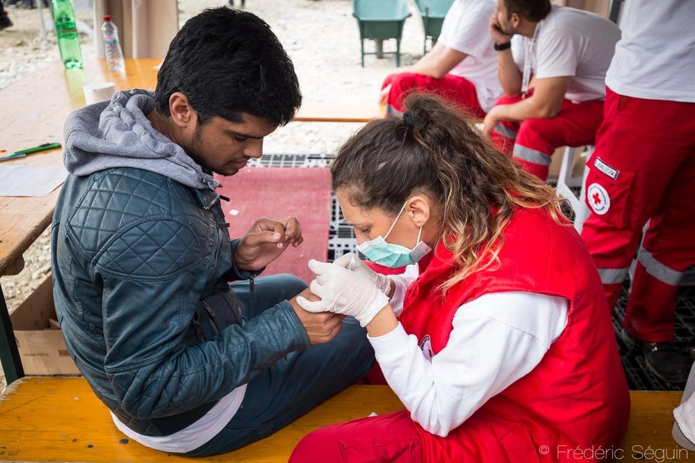 Une docteure de Croix Rouge Macédonienne traite un réfugié ayant souffert des conditions difficiles sur la route. Gevgelija, Macédoine