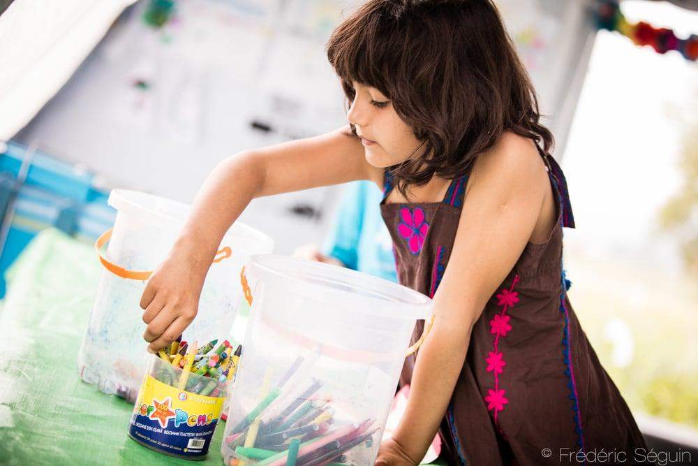 Une jeune fille prend le temps de colorier et de s'amuser un peu durant le long périple en s'arrêtant à la tente d'UNICEF dans le camp de transit. Gevgelija, Macédoine.