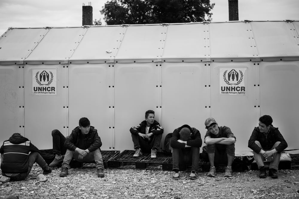 A group of refugees waits in front of a shelter provided by UNHCR. The High Commission for the Refugees from the UN is the organisation that provides most of the shelters in the camps in many countries. Gevgelija, Macedonia (FYROM).