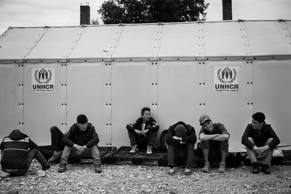 Des réfugiés attendent le train au camp de transit en se reposant devant une tente. UNHCR, l'agence de gestion des réfugiés de l'ONU fournit presque toutes les tentes des camps de transit dans les différents pays. Gevgelija, Macédoine.