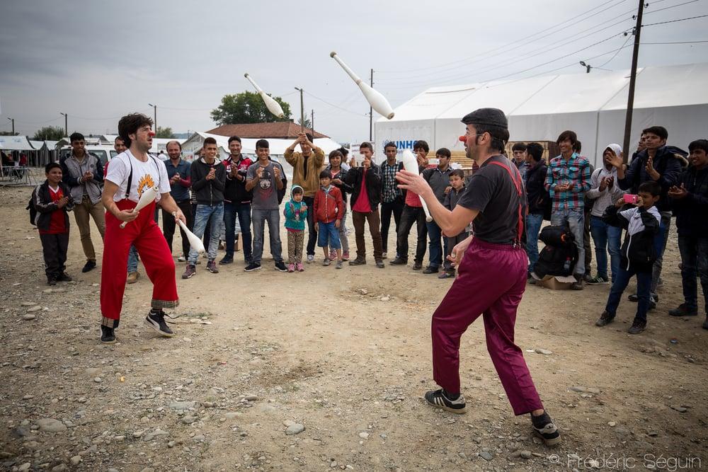 Deux clowns de Clowns Sans Frontières changent les idées d'une petite audience de réfugiés, jeunes et vieux en faisant étalage de leurs talents de jongleurs. Gevgelija, Macédoine.