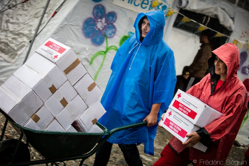 Two volunteers carry food as the rain pours down on them. Refugees continue to travel even in the harshest weather conditions, so do the volunteers. Gevgelija, Macedonia (FYROM).