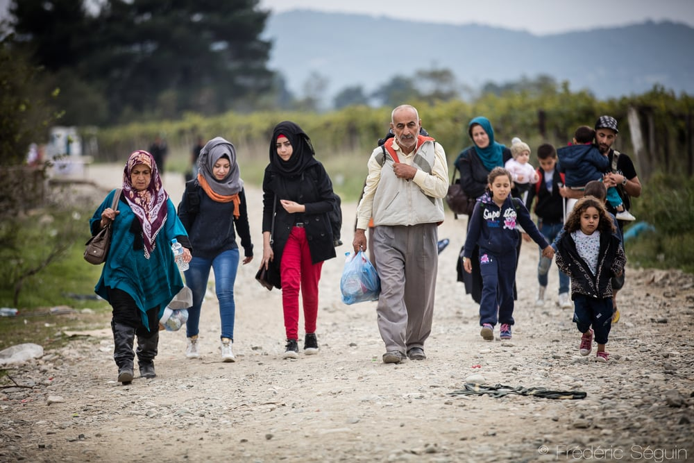 A family of refugees walks in the fields separating the two transit camps. It takes about 15 to 20 minutes to cross the distance. Gevgelija, Macedonia (FYROM).