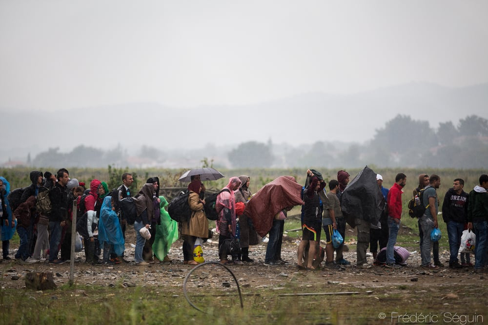 Under the rain, a group of refugees waits outside the camp. Rules do not change depending on the weather conditions which can make life really difficult for refugees who are often not prepared. Gevgelija, Macedonia (FYROM).