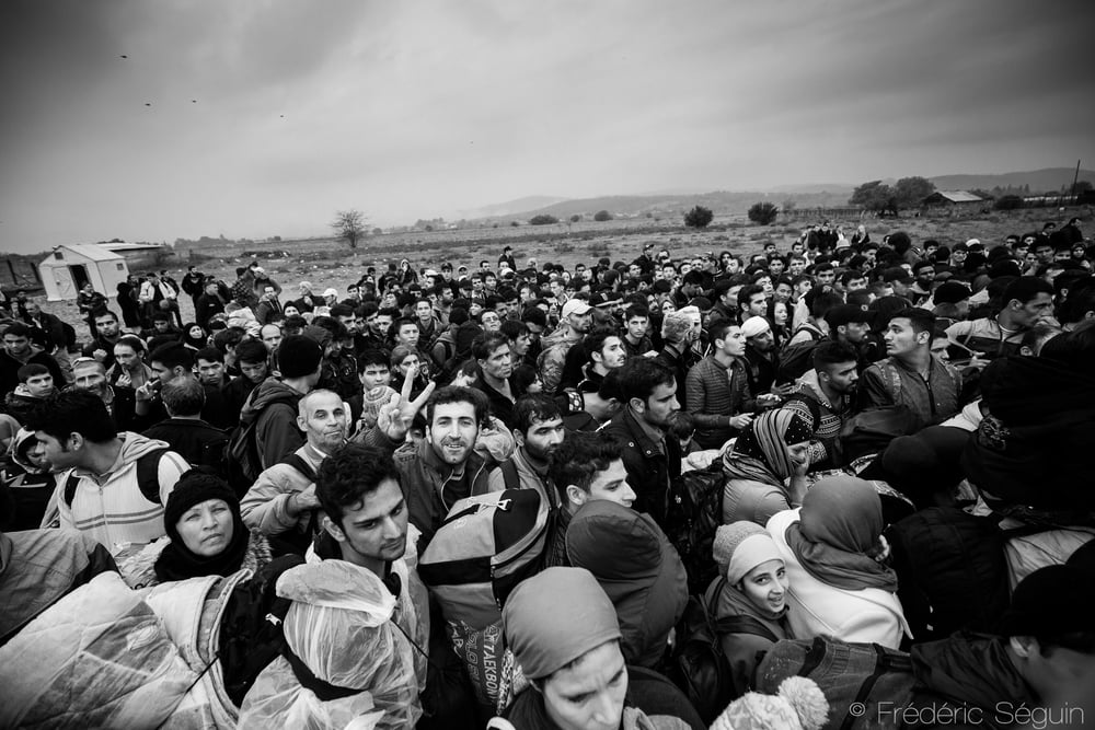 A crowd of refugees attempts to enter by force in the camp and a man still smiles at the camera despite the chaos. Even if everyone will eventually enter there are sometimes agitation and panic in big crowds. Gevgelija, Macedonia (FYROM).