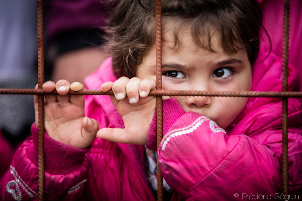 A little girl cries as she is holding the fence outsidethe camp, stuck in the chaos of the crowd. Children are the most vulnerable in these situations that they don't even understand.Gevgelija, Macedonia (FYROM).