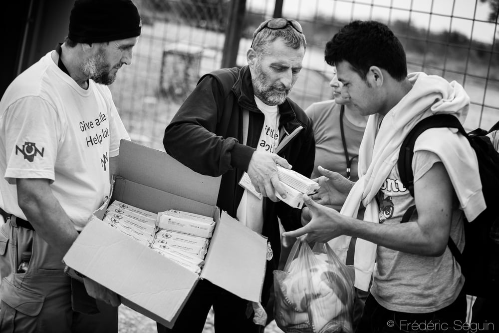Volunteers give packed food to refugees as they enter the camp. The first welcoming sight in the camp is always the kind volunteers and NGO workers, handing out what will be the only source of food for the refugees.Gevgelija, Macedonia (FYROM).