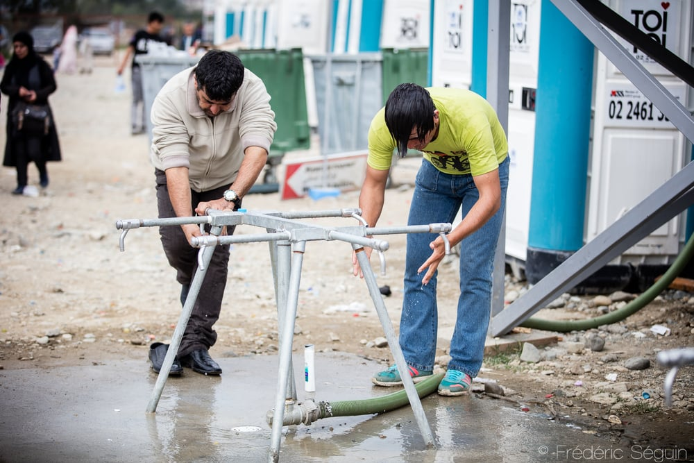 Two men wash themselves at the temporary showers installed by UNHCR. Lack of hygiene is a difficult challenge for the refugees and many camps try to propose solutions.Gevgelija, Macedonia (FYROM).
