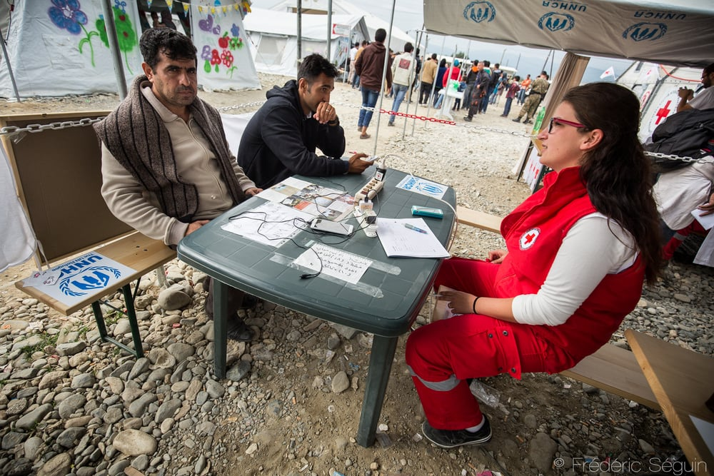Two men charge their cellphones and contact their families in the tent of Macedonian Red Cross which also provides free internet connection. Gevgelija, Macedonia (FYROM).