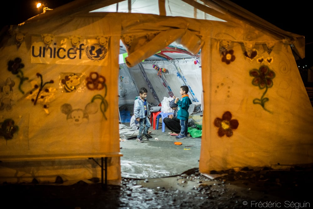 Two kids play in the UNICEF tent during the night. This area provides some playtime and a child friendly area. Gevgelija, Macedonia (FYROM).