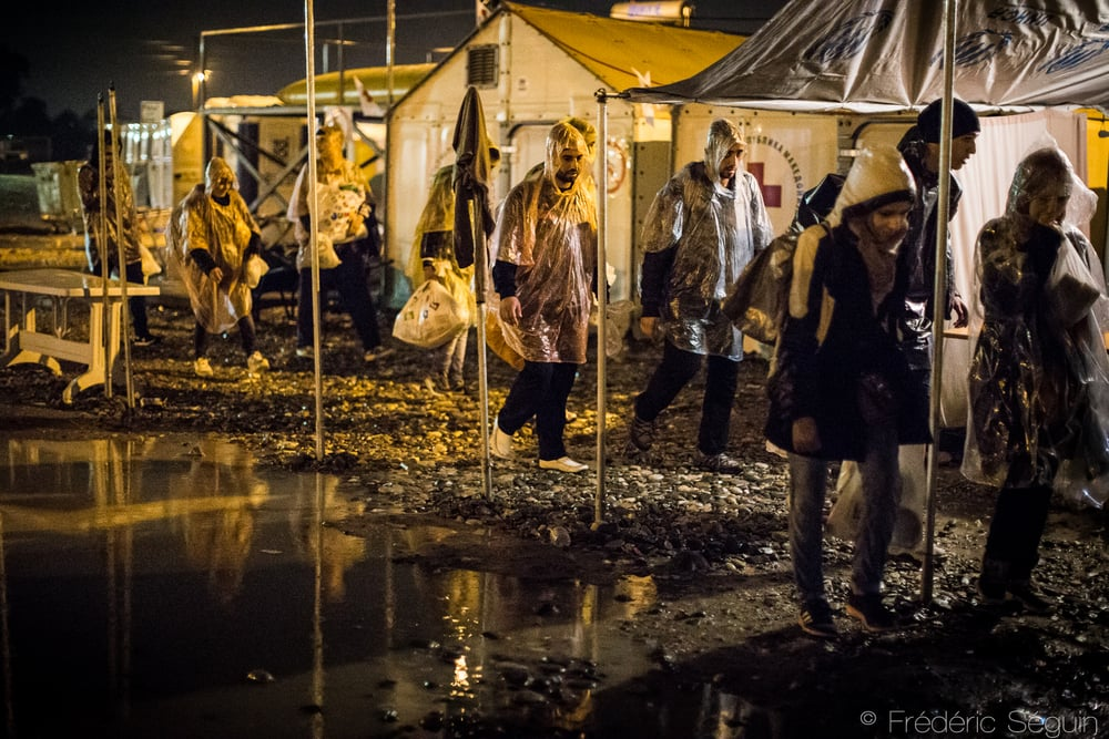 A group of refugees walk in the camp by night and under heavy rain. The water accumulates in the camp and creates many problems.Gevgelija, Macedonia (FYROM).
