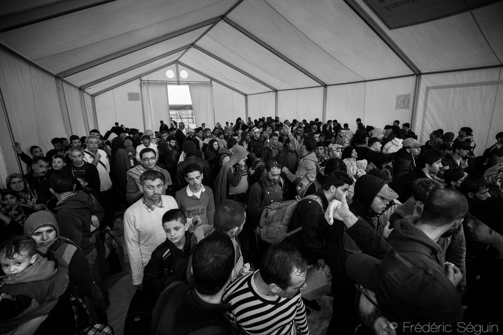 A tent is filled with refugees waiting for the train to arrive and trying to hide from the rain. These big tents provided by UNHCR are rudimentary but helps to protect from the bad weather.Gevgelija, Macedonia (FYROM).