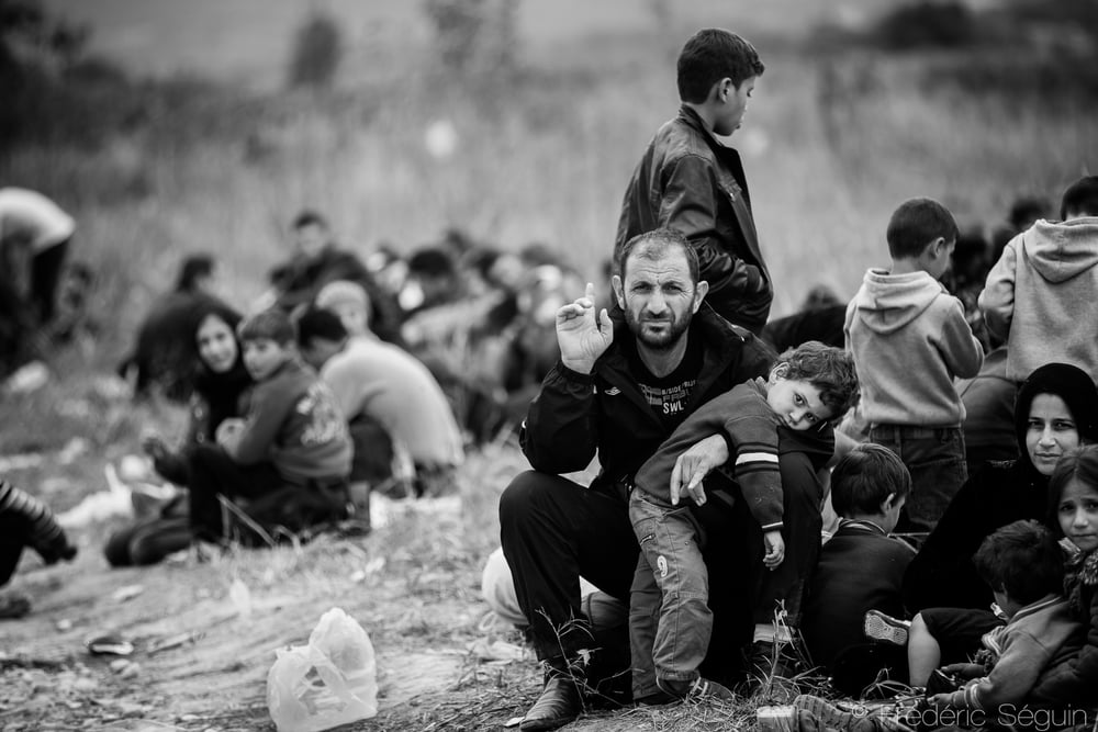 A young boy rests on his father as the group of refugees must wait outside until being allowed in the transit camp.Gevgelija, Macedonia (FYROM).