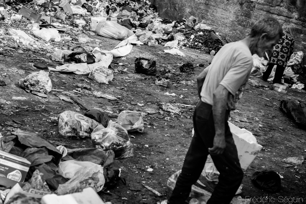 Man and woman searching in the garbage left outside in the streets of the Palestinian district Shatila. Beirut, Lebanon.