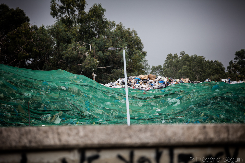 A huge pile of garbage in more than full improvised landfill is barely hidden under a green tarp in Karantina area. Beirut, November 2015.