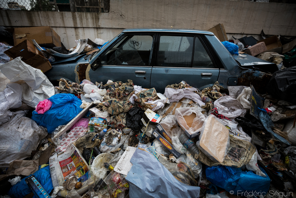 A car is submerged under a pile of garbage. Impossible to know if it is a part of the garbage or a victim. Beirut, Lebanon. November 2015.