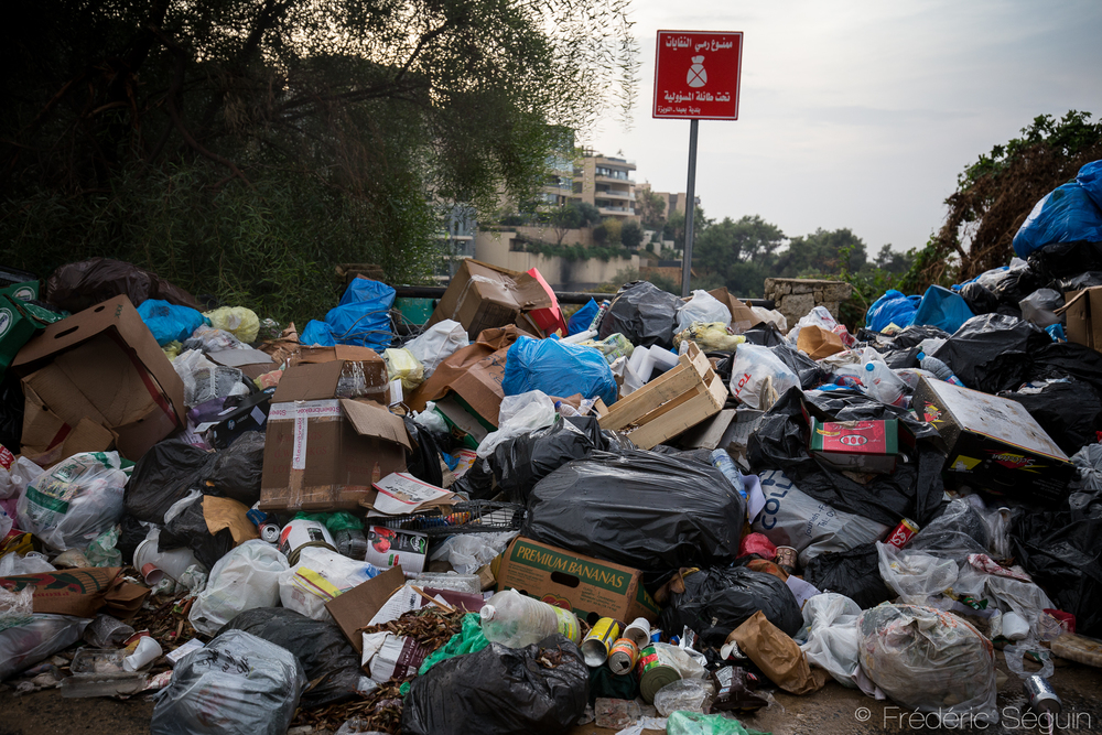 Ironically, a sign claiming the interdiction to throw garbage in the area sits on top of a huge pile of trash. Citizens of Beirut have no other option than to dump their garbage in improvised landfill, often on the side of the roads until the city infrastructures are up again. Baabda area, Beirut, Lebanon. November 2015.