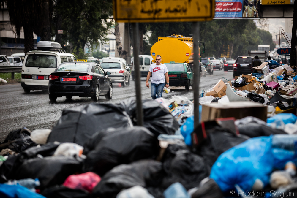 A man must walk in the street because sidewalks serve as an improvised dumping site for the trash. Beirut, Lebanon. November 2015.