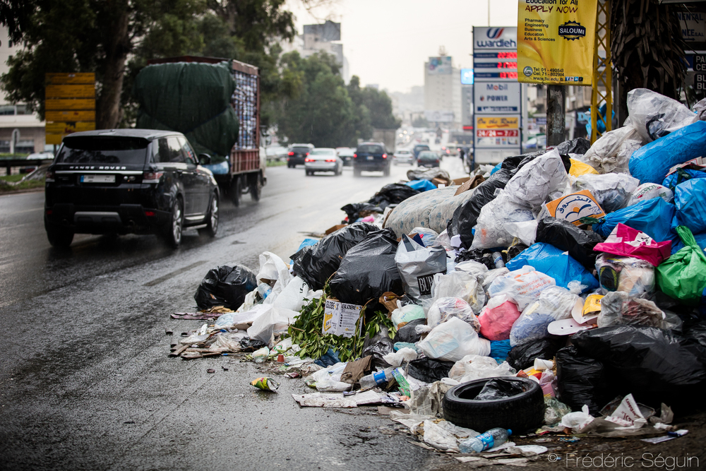 Cars must be careful to go around the piles of garbage flowing in the streets of the city. It always creates an impressive contrast to see the luxury cars in these situations. Beirut, Lebanon. November 2015.