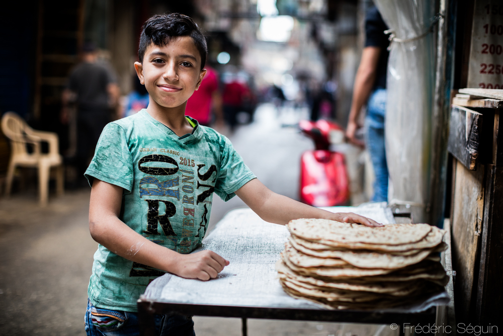 A young boy working in a bakery with a proud look on his face.