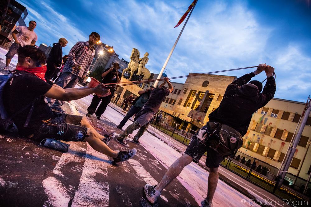 Face au parlement, des manifestants lancent des ballons de peinture à l'aide de slingshots artisanaux.