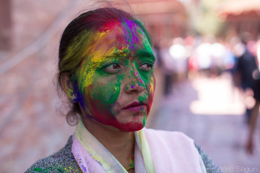 Une femme avec le visage complètement recouvert de peinture. Jouer à la Holi est ouvert à tous, jeunes et moins jeunes, touristes et népalais.