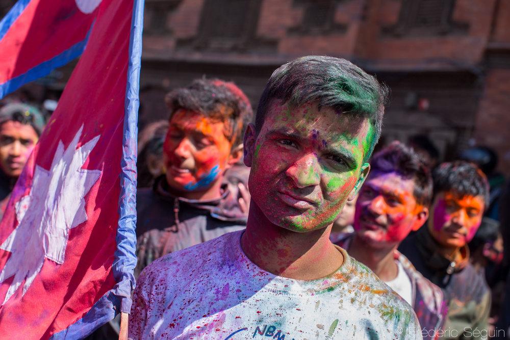 Un homme célèbre la Holi en portant le drapeau du Népal.