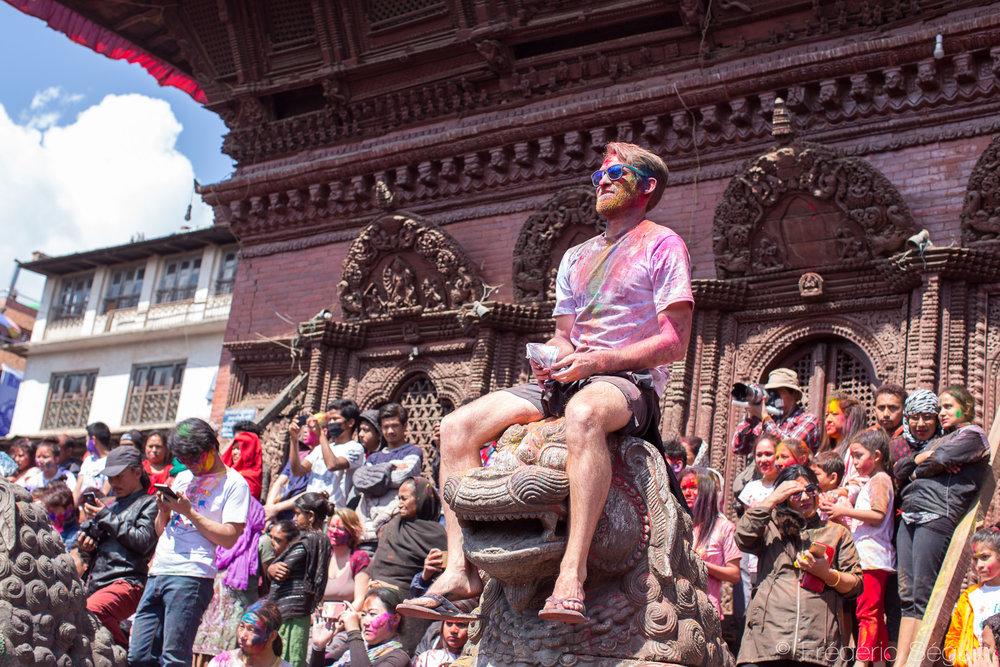 Un touriste célébrant la Holi est assis sur une statue d'un tes temples de la place du Dârbar.