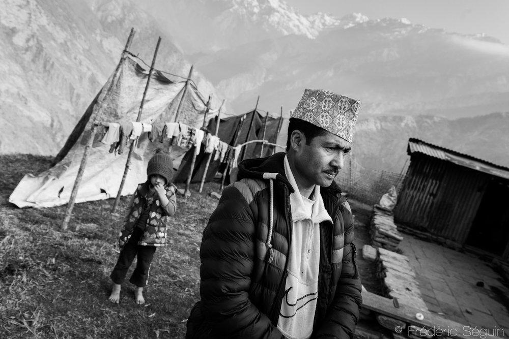 Faisant partie de la caste des orfèvres, une caste inférieure, cet homme affirme qu'il n'a reçu aucune aide de la part du gouvernement. Il s'arrange avec les moyens du bord pour protéger sa maison des intempéries. La météo est difficile et changeante en montagnes. Barpak, Népal. 26 mars 2017.