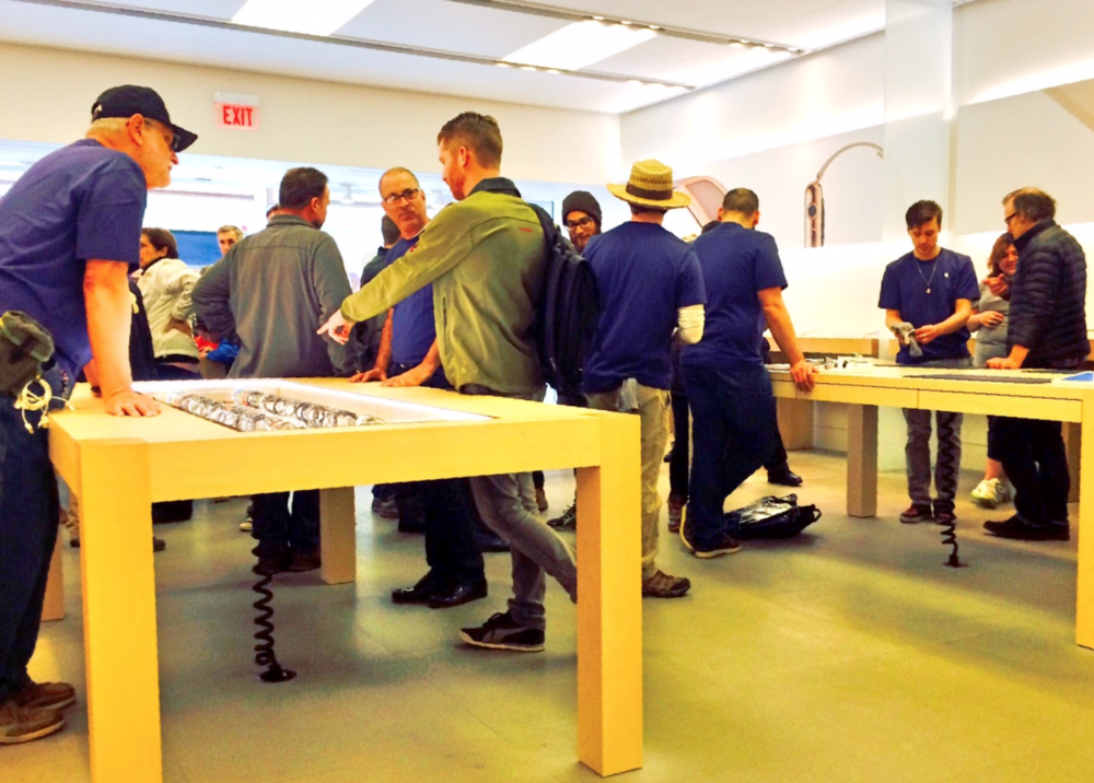 Apple Watch display table on left with try-on and demo table on the right. Additional try-on and demo spots were located alongside each wall.