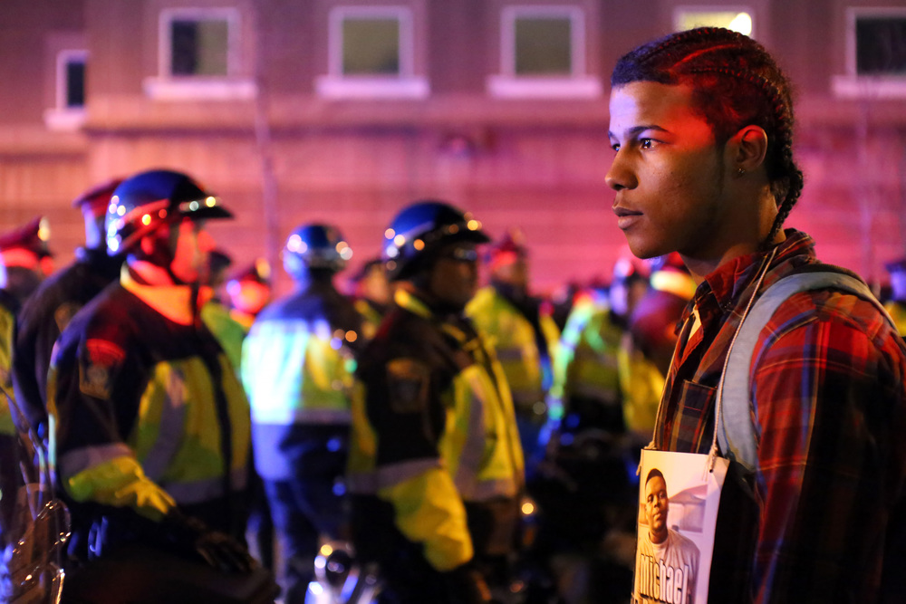 Emerson Brandao, from Roxbury, MA, stands in front of officers during a protest in Boston, MA, on November 25, 2014, in response to the failed indictment of police officer Darren Wilson for the murder of Mike Brown in Ferguson, MI.