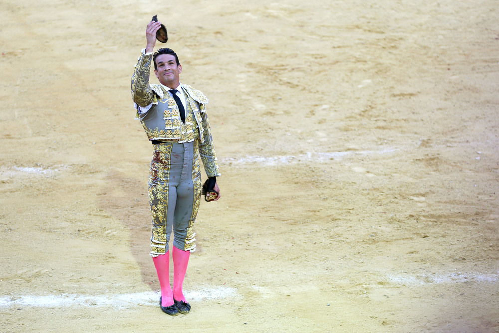 "José María Manzanares turns to the crowd holding the slain bull's ears - his reward for a strong performance in the eyes of the audience and the bullfight's president. The victorious matador, or ""torero,"" is then carried out of the arena on the shoulders of his ecstatic supporters."
