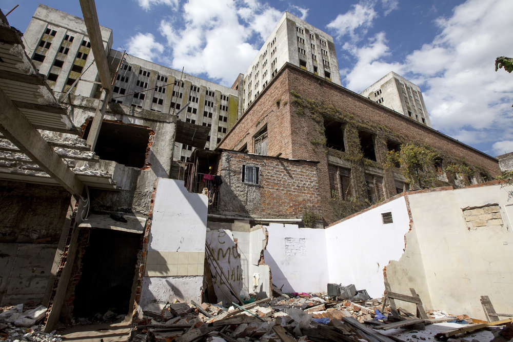 The imposing Elefante Blanco, or White Elephant, towers over the rubble of former homes of low-income families, in the Argentine neighborhood of Villa Lugano, in southern Buenos Aires, on Nov. 22, 2017. The Elephant, built during the first presidency of Perón, was destined to be the largest hospital in Latinamerica.