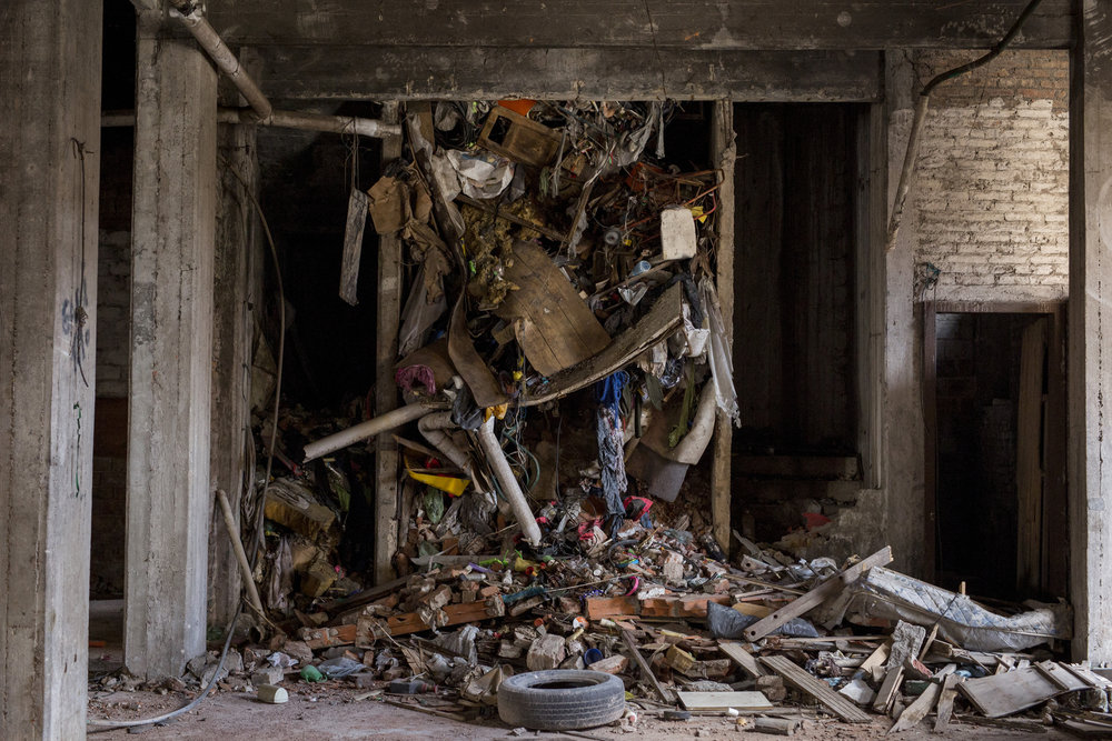 """Detail of the inside of an elevator shaft. Amongst the broken bricks, oxidised nails, and contaminated water, lie the old TV sets, sofas, chairs, cabinets, deflated footballs, glass bottles, unprotected wires, and, as one of the residents described them, """"cat-sized rats""""."""