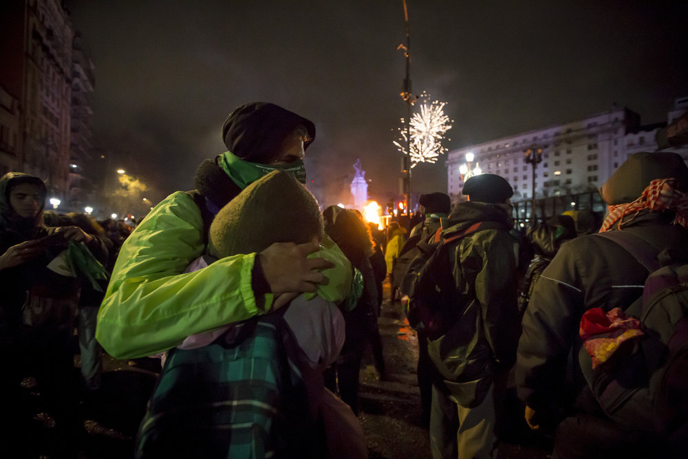 "A couple embrace after the final vote on the abortion bill – rejected 38 against, 31 in favor – was announced, on Aug. 9, 2018, in Buenos Aires, Argentina. On the other side of the Congress Plaza, supporters of the ""Save Both Lives"" campaign set off fireworks."