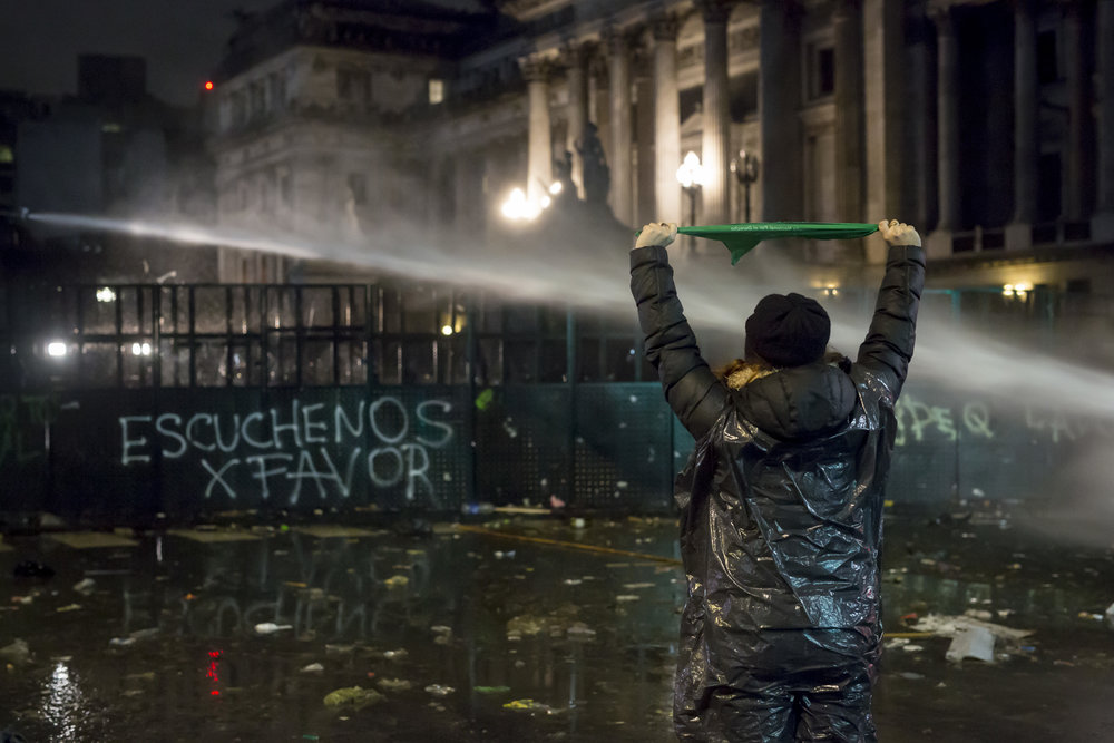 "A woman shows off the green handkerchief – the symbol of the pro-choice movement – as police use water cannons to disperse the small crowd that remained after the vote on Aug. 9, 2018, in Buenos Aires, Argentina. The sign in the background says ""Please, hear us""."